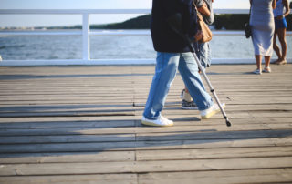elder man with cane on boardwalk