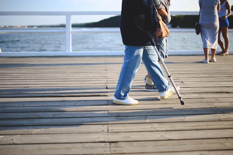 elder man with cane on boardwalk
